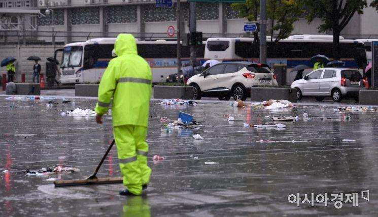전국 대부분 지역에 비가 내린 7일 서울 광화문광장에서 환경미화원이 전날 행사에서 나온 쓰레기를 치우고 있다./김현민 기자 kimhyun81@