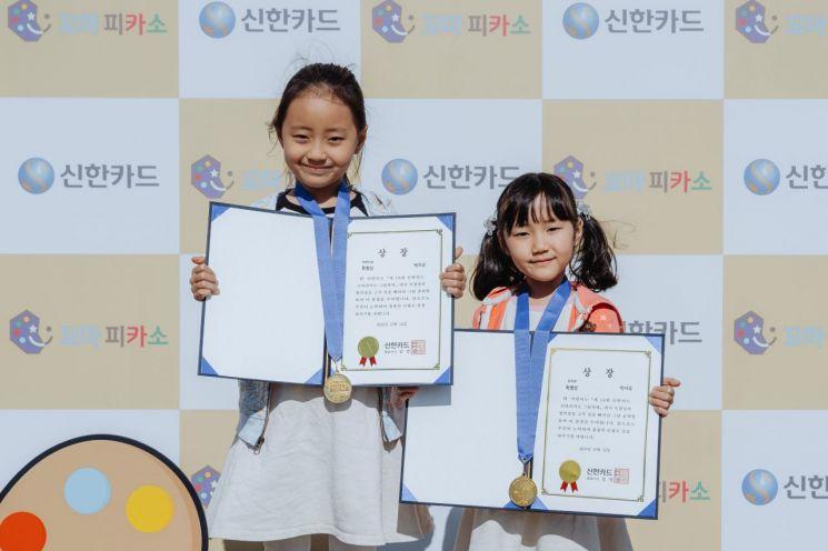 신한카드는 지난 12일 '제 18회 신한카드 꼬마피카소 그림축제'를 개최했다고 13일 밝혔다. 저학년부, 유치부 특별상을 수상한 두 어린이가 메달과 상장을 들고 기념촬영하고 있다. 사진=신한카드 제공