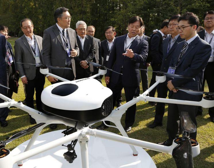 동현수 ㈜두산 부회장(앞줄 왼쪽 두번째)이 16일 DLI연강원에서 열린 제품 출시 행사에서 이두순 두산모빌리티이노베이션 대표(앞줄 왼쪽 첫번째)와 DS30을 살펴보고 있다.