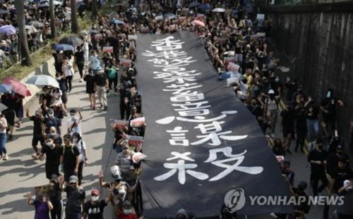 홍콩 시위대가 '홍콩 경찰이 짐승처럼 사람을 죽인다'고 쓴 플래카드를 들고 행진하고 있다.(사진출처=연합뉴스)