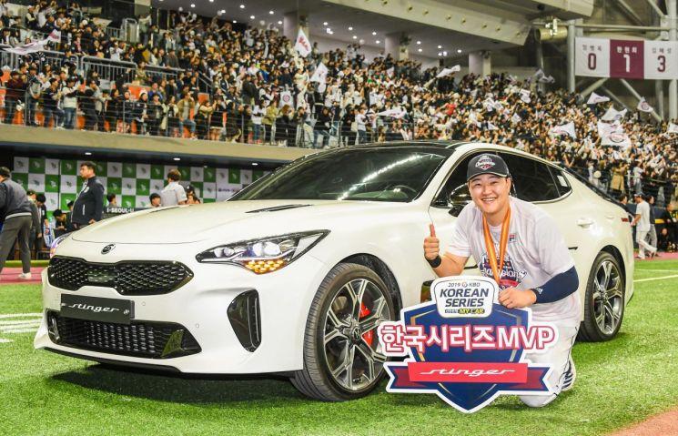 기아자동차가 한국시리즈 MVP를 수상한 두산베어스 오재일 선수에게 스팅어를 전달했다. 사진은 오 선수가 부상으로 받은 스팅어와 함께 기념촬영을 하고 있는 모습/사진=기아차
