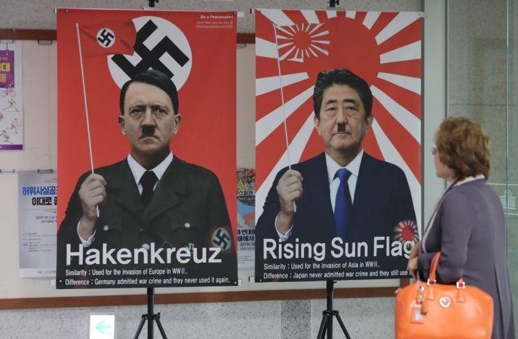 지난달 1일 국회 의원회관에서 열린 '반평화, 반환경 2020도쿄올림픽 대응을 위한 토론회'에 참석한 재미한인회장단이 복도에 전시된 욱일기 관련 포스터를 바라보고 있다.[이미지출처=연합뉴스]