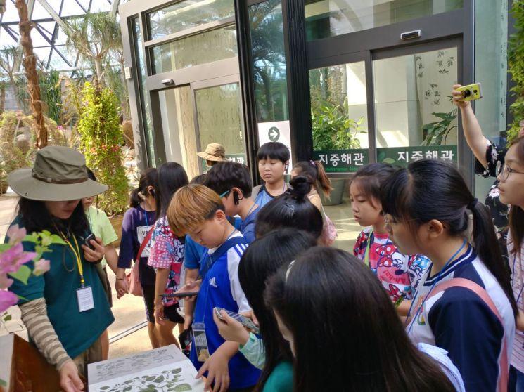 서울식물원의 온실 '지중해관'을 찾은 학생들이 투어프로그램 도중 해설사의 설명에 귀기울이고 있다. / 서울식물원 제공