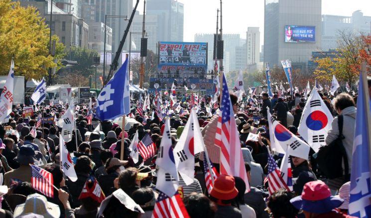 9일 오후 서울 광화문 교보빌딩 앞에서 문재인하야범국민투쟁본부 주최로 열린 대한민국 바로 세우기 국민대회에서 참가자들이 구호를 외치며 태극기와 손팻말을 흔들고 있다. (사진=연합뉴스)
