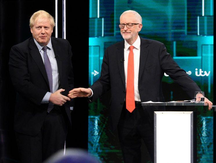 19일 밤(현지시간) 영국 ITV 토론회에 참석한 보리스 존슨 총리(왼쪽)와 제러미 코빈 대표가 토론 분위기를 바꾸고자 하는 사회자의 요구에 따라 어색한 표정으로 악수를 나누고 있다. [이미지출처=로이터연합뉴스]