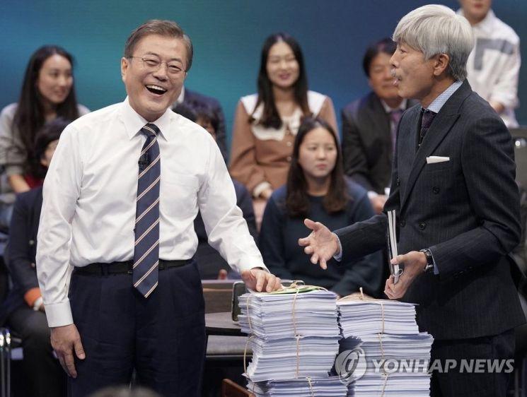 문재인 대통령이 19일 오후 서울 상암동 MBC에서 '국민이 묻는다, 2019 국민과의 대화' 종료 후 시간 관계상 받지 못한 질문지를 전달받고 있다. [이미지출처=연합뉴스]