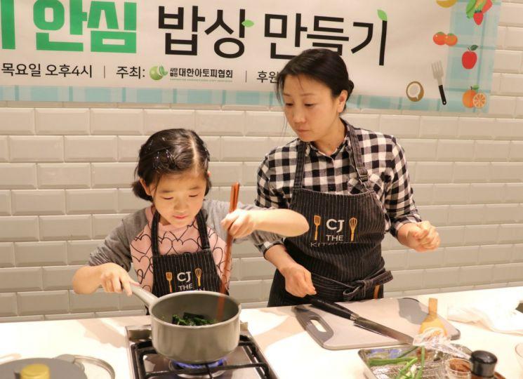 21일 서울 중구 동호로 CJ제일제당 사옥내 'CJ 더 키친'에서 열린 'BYO 유산균과 함께하는 아토피 안심 밥상 만들기' 쿠킹클래스에 참가한 가족이 요리를 하고 있는 모습.
