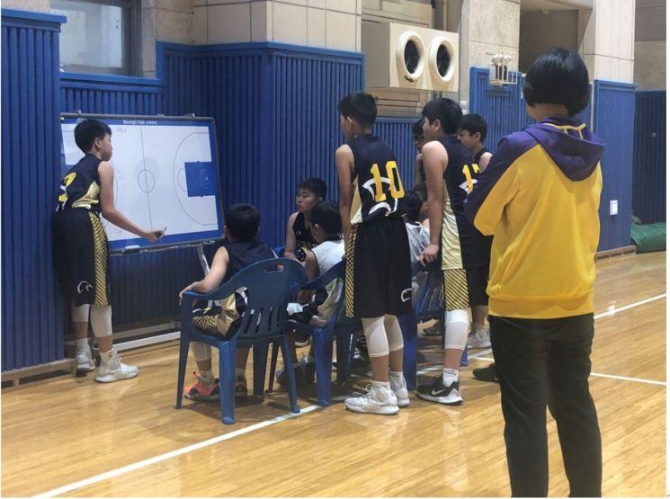 임혜영 코치가 연가초등학교 농구부 선수들끼리 전술회의를 하는 모습을 지켜보고 있다.