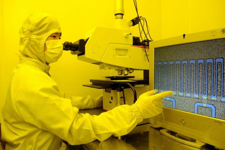 ETRI 연구진이 개발한 질화갈륨 전력소자 칩을 광학현미경을 통해 확인하고 있다.