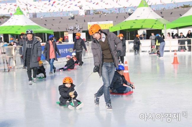 광주광역시청 앞 문화광장 야외썰매장에서 부모들이 아이가 탄 썰매를 끌어주고 있다.