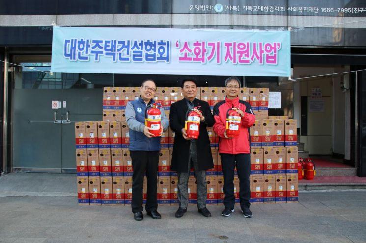 박재홍 대한주택건설협회 회장(가운데)이 15일 따쓰한 채움터에 소화기를 전달한 뒤 기념촬영을 하고 있다. (사진=대한주택건설협회)