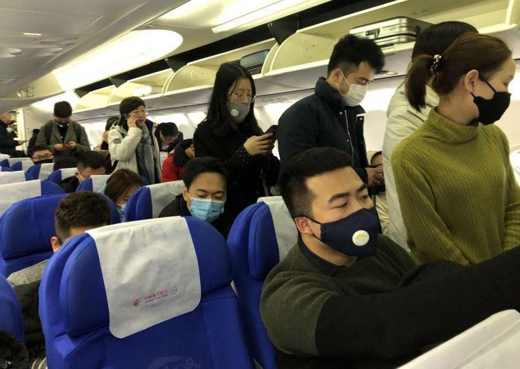 21일 중국 상하이를 출발해 우한으로 향하는 항공기에 탄 승객들이 신종 코로나바이러스 감염을 막고자 마스크를 쓰고 있다.(이미지 출처=연합뉴스)