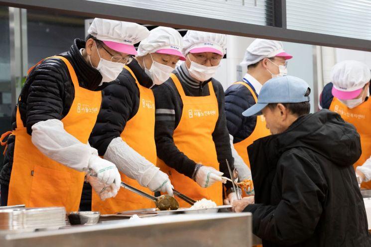 은성수 금융위원장(왼쪽부터), 이계문 서민금융진흥원장 등 자원봉사자들이 20일 식사를 배식하고 있다.