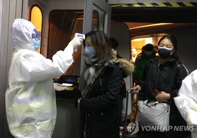 지난 22일(현지시간) 중국 우한에서 온 승객들을 대상으로 한 베이징 공항 당국의 체온 검사 / 사진=연합뉴스