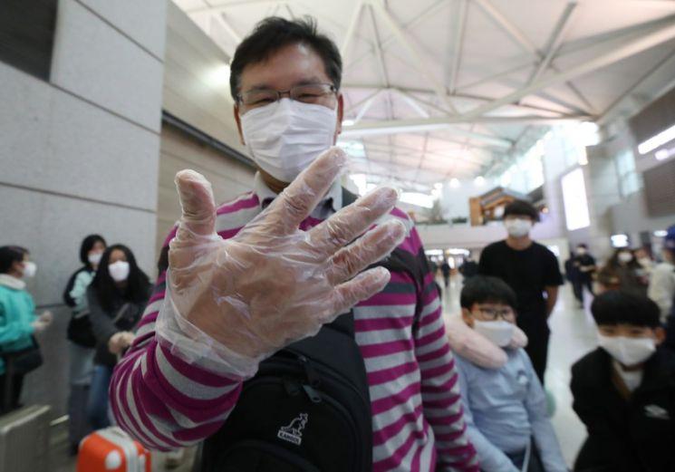 국내에서 신종 코로나바이러스 감염증인 '우한 폐렴' 네 번째 확진환자가 발생한 27일 오후 인천국제공항 1터미널에서 한 출국자가 출국심사대로 향하며 비닐장갑을 낀 손을 보여주고 있다. <사진=연합뉴스>