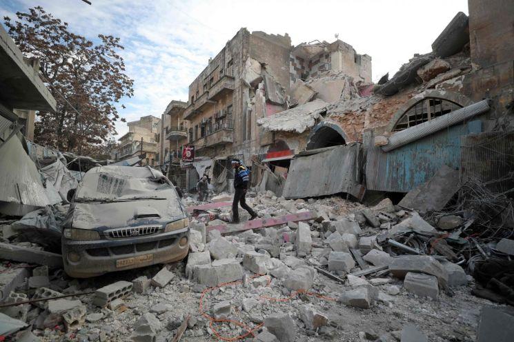 지난 15일(현지시간) 시리아 정부군의 공습을 받은 마지막 반군 거점 이들립주(州) 이들립시(市)에서 한 남성이 건물 잔해 속을 걷고 있다. <사진=AFP연합>