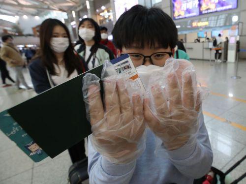 국내에서 신종 코로나바이러스 감염증인 '우한 폐렴'  네 번째 확진환자가 발생한 27일 오후 인천국제공항 1터미널에서  한 어린이가 출국심사대로 향하며 비닐장갑을 낀 손을 보여주고 있다.  <사진=연합뉴스>