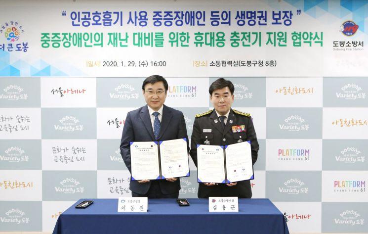 이동진 도봉구청장(왼쪽)과 김용근 도봉소방서장(오른쪽)이 휴대용 충전기 지원 업무협약을 체결하는 모습