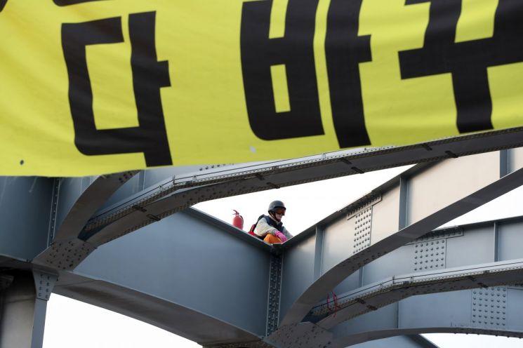 14일 오전 한 남성이 한강대교 아치 위에 올라가 시위를 하고 있다. [이미지출처=연합뉴스]
