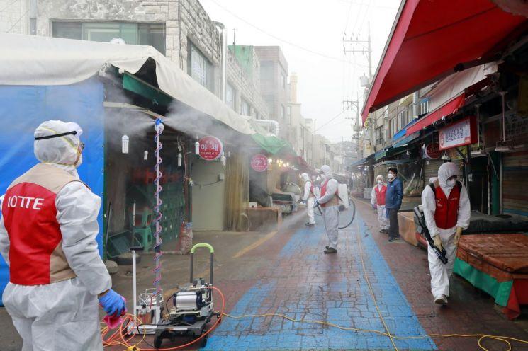 롯데월드타워 임직원들이 14일 서울 송파구 전통시장을 찾아 방역 작업을 실시하고 있다, (사진=롯데물산 제공)