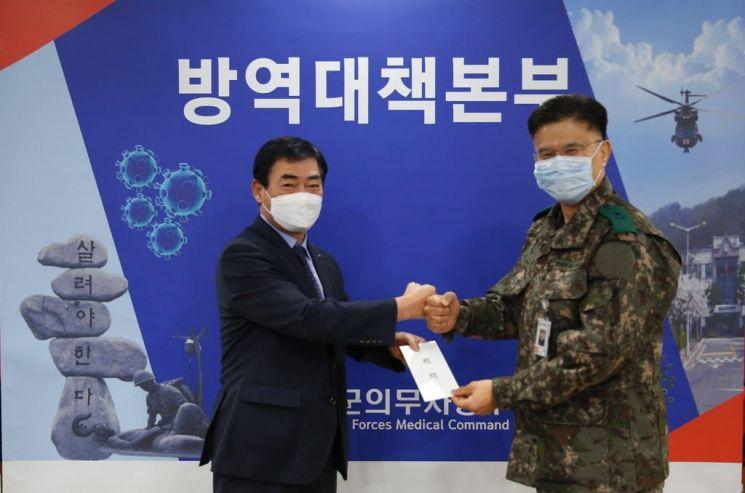 김도호 군인공제회 이사장(왼쪽)이 9일 국군의무사령부를 방문해 코로나19 차단을 위해 헌신하고 있는 장병들을 위한 위문금을 전달하고 있다.
