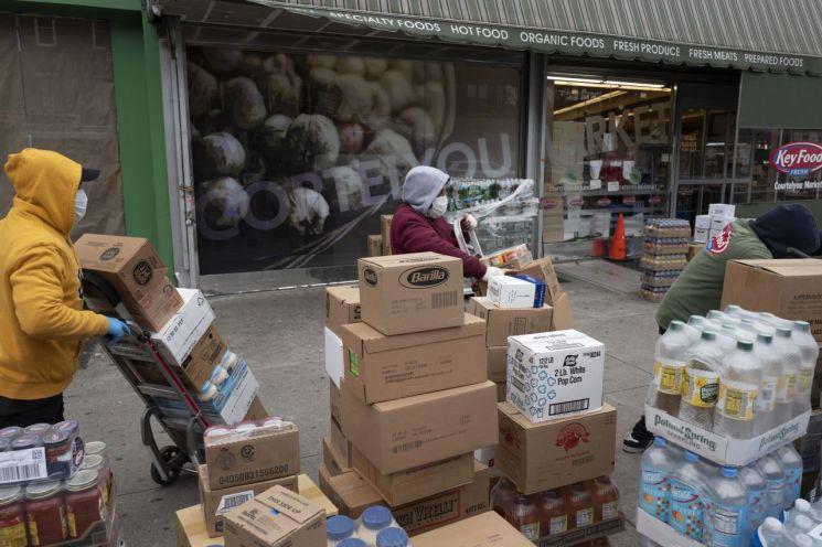 사재기 수요에 대비한 식료품을 입고하고 있는 미국 뉴욕의 한 대형 슈퍼마켓 직원들의 모습 [이미지출처=AP연합뉴스]