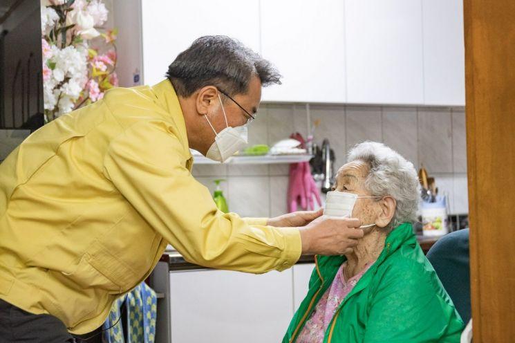 김선갑 광진구청장이 어버이날을 맞아 어르신에게 마스크를 끼워주고 있다.