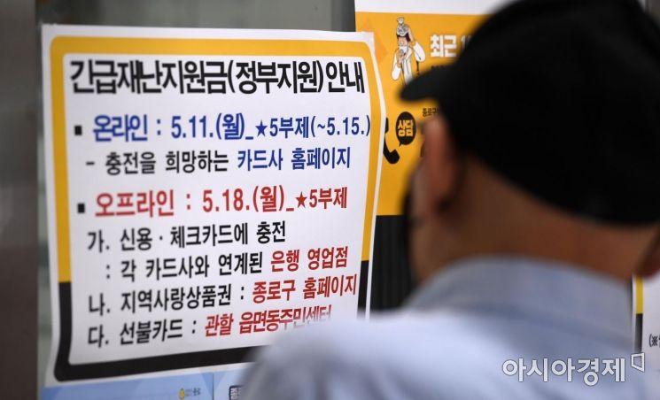 정부의 긴급재난지원금 신용·체크카드 충전 신청이 11일 오전 7시 9개 카드사 홈페이지를 통해 시작됐다. 공적 마스크 5부제와 마찬가지로 신청에는 요일제가 적용되고 16일부터는 언제든 신청할 수 있게 바뀐다. 지원금은 1인 가구 40만원, 2인 가구 60만원, 3인 가구 80만원, 4인 이상 가구 100만원이다. 사진은 이날 서울 종로구의 주민센터를 찾은 한 시민이 지원금 안내문을 바라보는 모습./김현민 기자 kimhyun81@