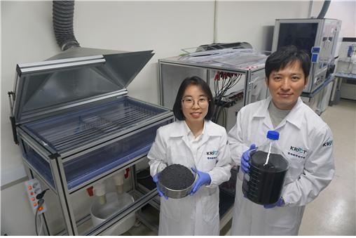 한국화학연구원 이제욱 책임연구원(오른쪽)과 권연주 연구원(왼쪽)이 멀티 전극 시스템으로 생산한 그래핀 용액과 가루를 들고 사진을 촬영하고 있다. 두 연구원 뒤에 있는 장치가 차세대 전기화학 박리공정이 적용된 멀티 전극 시스템이다.