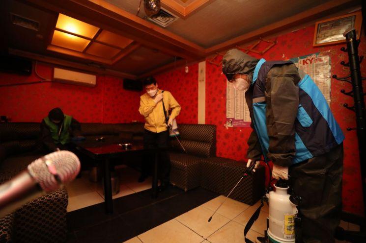 서울 중구청 관계자들과 광희동 주민자치센터 직원들이 관내 상업시설 방역을 하며 노래방을 방역하고 있다.<이미지:연합뉴스>