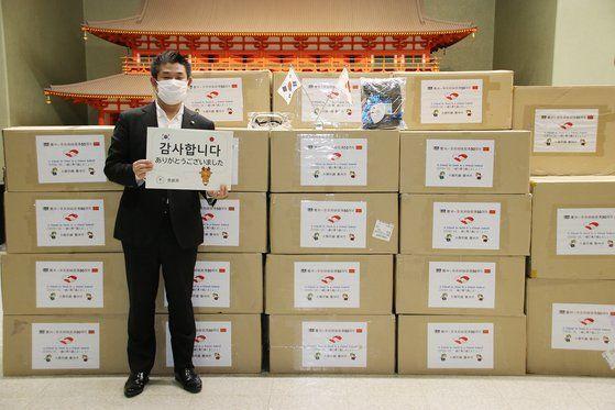 나카가와 겐 일본 나라시장이 경주시가 보낸 방역물품을 받은 후 '감사합니다'란 팻말을 들고 서 있는 모습. / 사진=경주시