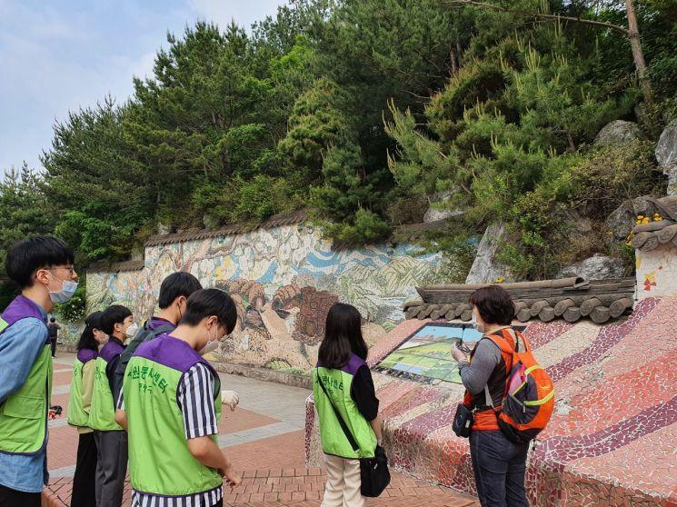 23일 '자원봉사야 놀~자' 봉화산 코스에 참여한 학생들이 향토문화해설사의 설명을 듣고 있다