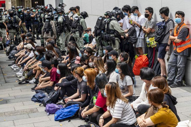 홍콩 경찰이 코즈웨이 베이 지구에서 국가보안법 제정에 항의하는 시위 참가자들을 대거 붙잡아 둔 가운데 이들이 소지한 가방을 뒤지고 스마트폰을 살펴보고 있다.(홍콩 EPA=연합뉴스)