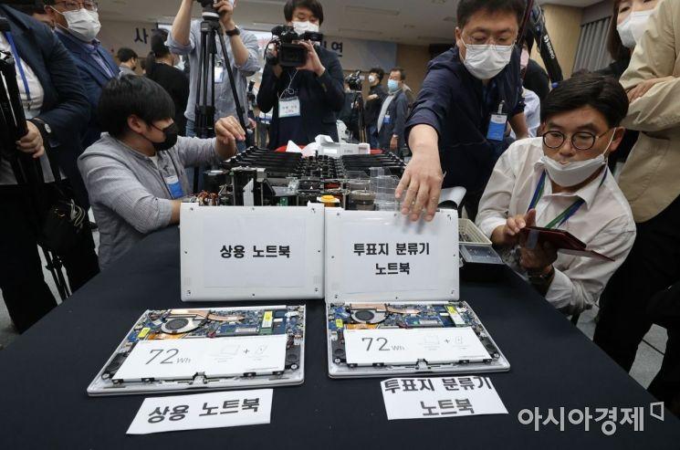 28일 오후 경기도 과천시 중앙선거관리위원회 대회의실에서 언론을 상대로 사전투표 투개표 및 개표 과정 공개 시연회가 열리고 있다. 투표지 분류기 노트북을 분해하고 있는 모습./김현민 기자 kimhyun81@