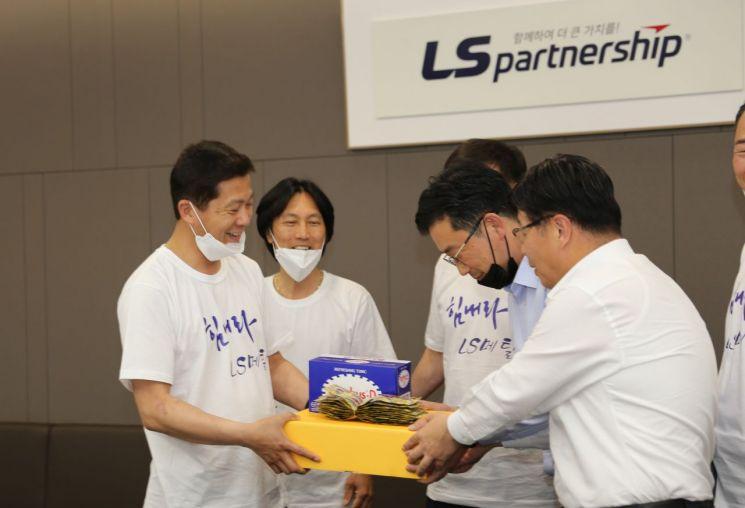 문창배 LS메탈 노조위원장(왼쪽)이 28일 서울 LS용산타워에서  영업사원들에게 빵과 음료를 전달하며 악수를 나누고 있다.  [사진=LS]