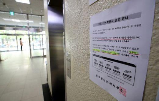 코로나19 확진 판정을 받은 강사가 근무한 학원이 위치한 서울 여의도 한 빌딩에 지난 25일 '코로나19 확진자 경유 안내문'이 붙어 있다. / 사진=연합뉴스