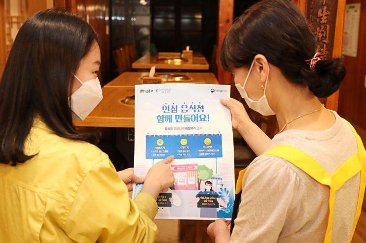 음식점 업주에게 캠페인에 대해 설명       하고 적극적인 참여를 독려하고 있다.