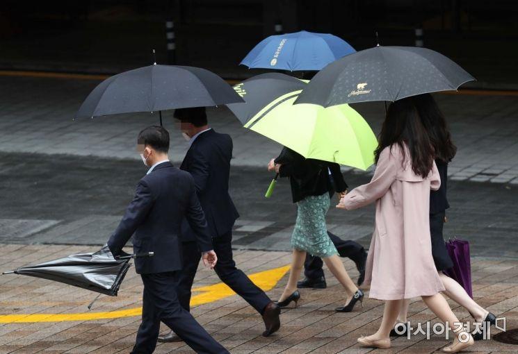 비가 내린 2일 서울 명동에서 우산을 쓴 직장인들이 점심식사를 위해 식당으로 향하고 있다. /문호남 기자 munonam@