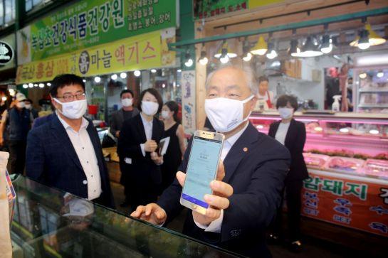 조봉환 소상공인시장진흥공단 이사장(오른쪽)이 4일 대전 서구 도마큰시장을 방문해 상인에게 모바일 온누리상품권을 보여주면서 물건을 구매하고 있다.