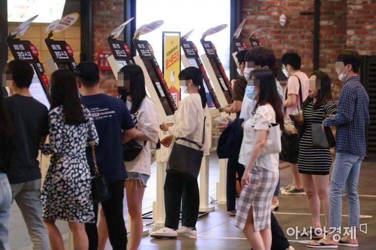 14일 서울 CGV 용산아이파크몰에서 시민들이 영화 관람을 위해 티켓을 구매하고 있다. 반값 할인권 배포와 신작 개봉, 무더운 날씨 등이 맞물리면서 침체에 빠져 있던 극장가가 조금씩 활기를 찾고 있다. /문호남 기자 munonam@