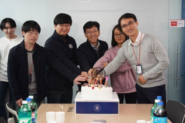 매출 100억원 달성 기념식에서 장기 근속자들과 장민호 디딤365 대표이사(오른쪽)가 케이크 자르기를 하고 있다. (제공=디딤365)