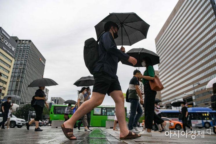 장마가 시작된 지난달 24일 서울 종로구 세종로 네거리에서 시민들이 우산을 쓰고 출근길에 오르고 있다./강진형 기자aymsdream@