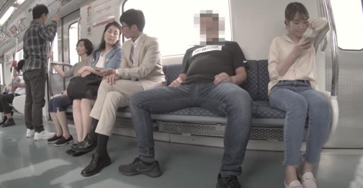 한 남성이 다리를 크게 벌린 채 지하철을 이용하고 있다. 남성 주변으로 불편한 표정을 짓고 있다. 사진=부산광역시 공식 유튜브 채널 캡처