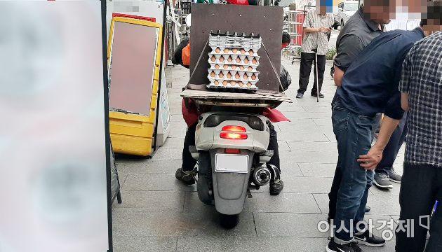 서울 한 번화가에서 배달용 오토바이가 짐을 싣고 인도로 주행하고 있다. 사진=한승곤 기자 hsg@asiae.co.kr