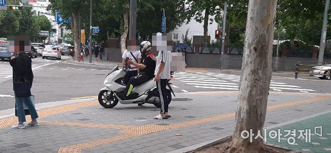 한 배달용 오토바이가 인도에 올라와 횡단보도 신호를 대기하고 있다. 오토바이 주변으로 통행을 하고 있는 시민들이 보인다. 사진=한승곤 기자 hsg@asiae.co.kr