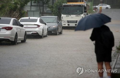 강원 영동지방을 중심으로 기록적인 폭우가 쏟아진 지난달 30일 오전 강릉 시내에서 시민이 출근길을 재촉하는 모습.사진=연합뉴스