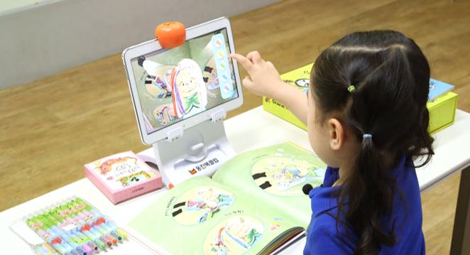 어린이가 증강현실(AR) 기술이 적용된 웅진씽크빅 인터랙티브북을 이용하고 있다.