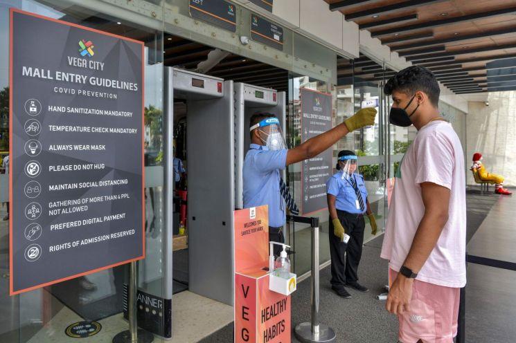 인도 방가로르의 한 쇼핑몰에서 보안 요원이 입장하는 고객의 체온을 측정하고 있다. [이미지출처=AFP연합뉴스]