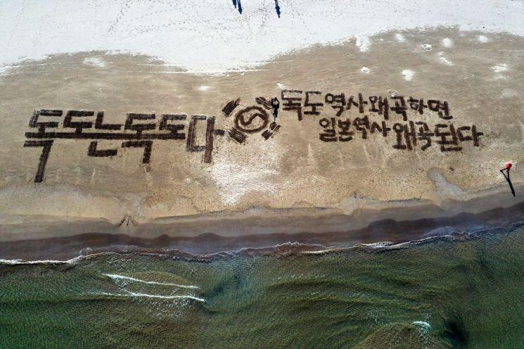 지난 4월26일 오후 경북 포항 영일대해수욕장에서 서예가 김동욱씨가 갈퀴로 독도 수호 글귀를 쓰는 행위예술을 하고 있다. (사진=연합뉴스)