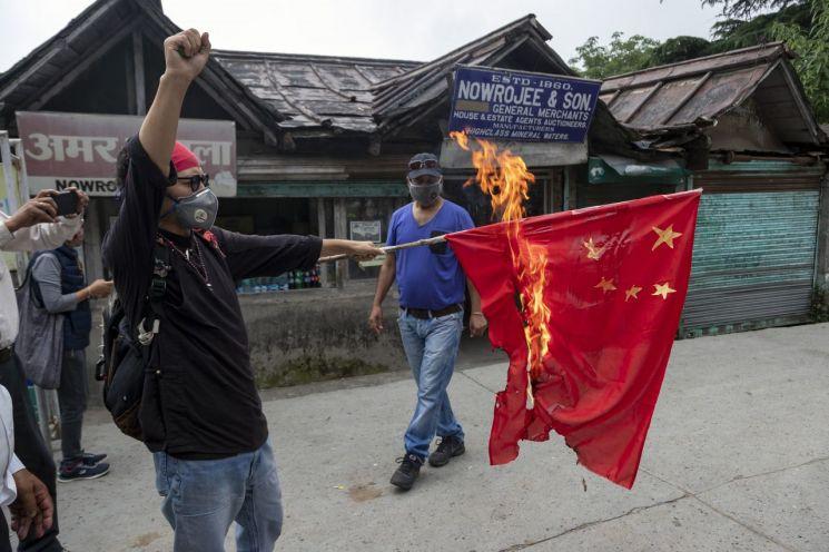 티벳 독립 운동가들이 중국 국기를 불태우고 있다. [이미지출처=AP연합뉴스]